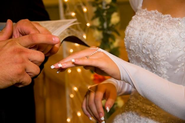 Marié mettre une bague de mariage sur le doigt de la mariée
