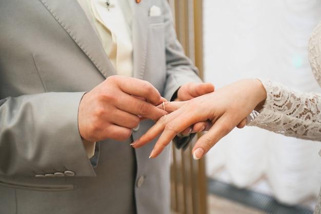 Le marié place l'anneau sur la main de la mariée. les mains des mariés.