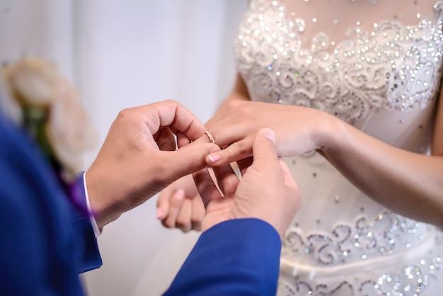 Le marié place la bague de mariage sur le doigt de la mariée