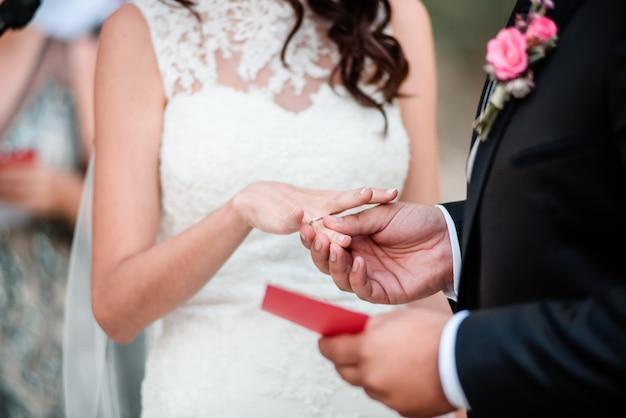 Le marié porte une alliance lors d'une cérémonie de mariage en plein air