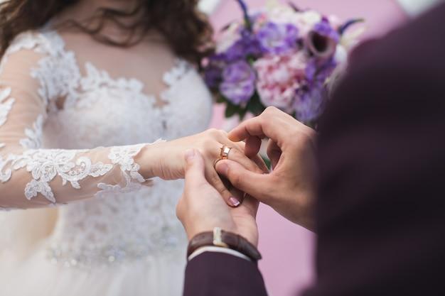 Le marié porte la bague mariée