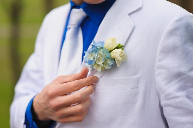 Le marié porte une boutonnière