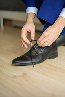 Le marié porte des chaussures en costume de mariage bleu