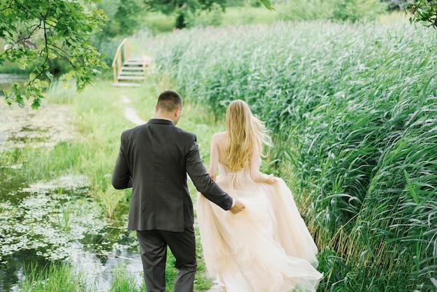Le marié soutient la robe de la mariée et ils avancent, vue de dos