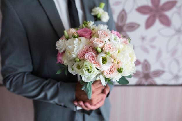 Marié tenant un bouquet de mariage de roses blanches, bouquet de fleurs blanches dans des mains masculines