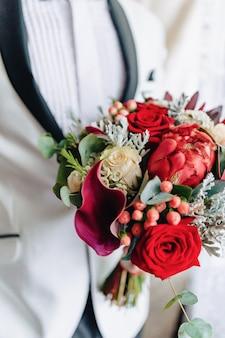 Le marié tient un bouquet de mariage dans ses mains