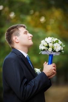 Le marié tient un bouquet de mariée à la main et lève les yeux