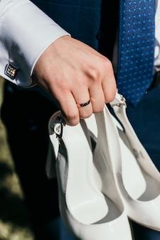 Le marié tient dans sa main les chaussures blanches du gros plan de la mariée.