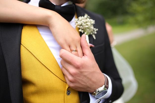 Le marié tient dans sa main la main de la mariée sur le doigt d'une bague de mariage en or
