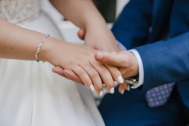 Le marié tient doucement la main de la mariée lors de la cérémonie de mariage