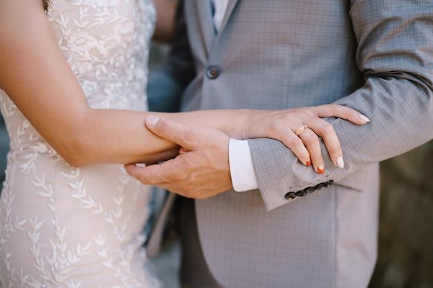 Le marié tient le gros plan du bras de la mariée