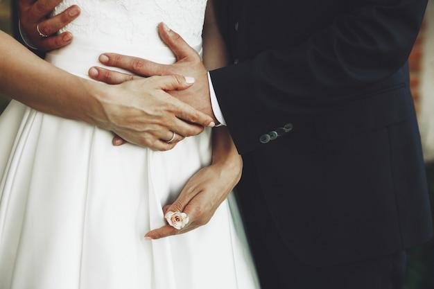 Le marié tient la jeune mariée alors qu'elle porte une petite rose à la main