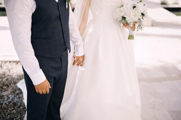 Le marié tient la main de la mariée dans une robe blanche avec un bouquet de fleurs