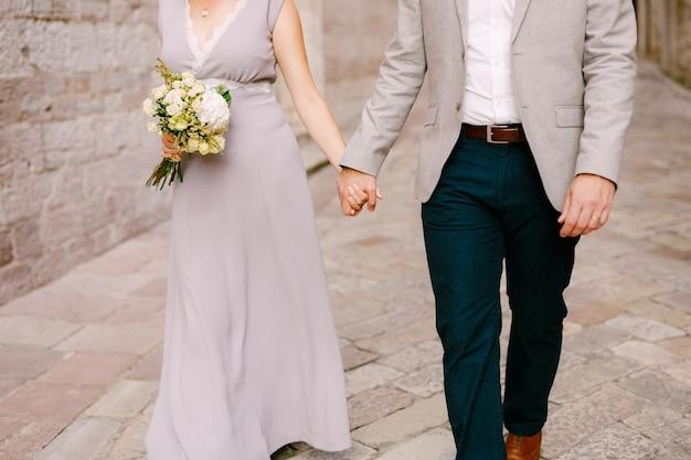 Le marié tient la main de la mariée dans une robe de mariée avec un bouquet de fleurs
