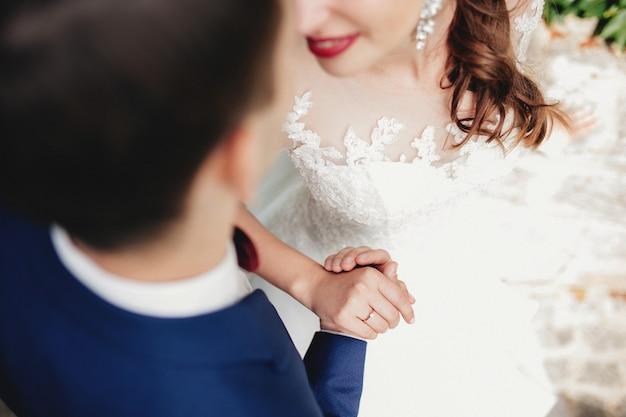 Le marié tient la main de la mariée en robe blanche