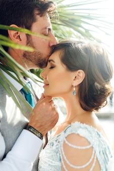 Marié tient la mariée tendre debout dans les feuilles vertes