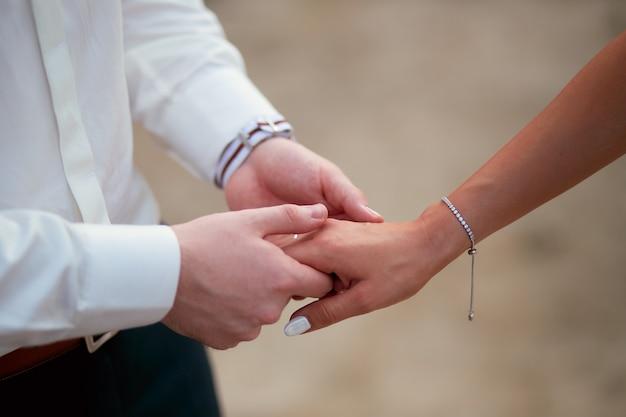 Le marié tient l'offre de la main de la mariée