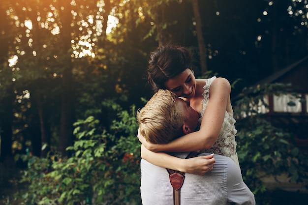 Le marié tient sa mariée dans ses bras quelque part dans la nature