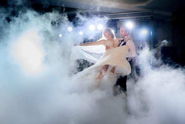 Le marié tourbillonne la mariée dans la fumée en dansant pour la première fois