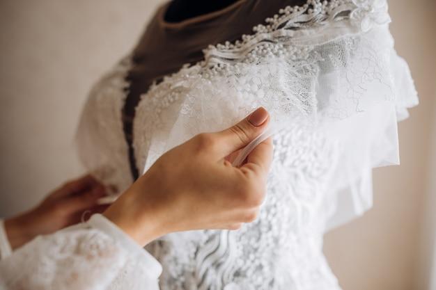 La mariée ajuste sa robe de mariée