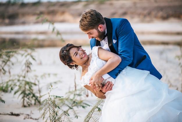 Mariée asiatique et marié caucasien ont du temps de romance et heureux ensemble