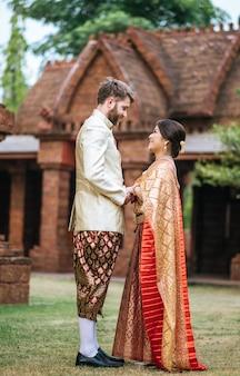 Mariée asiatique et marié caucasien ont du temps romantique avec la robe de la thaïlande