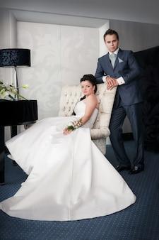 La mariée assise et le marié se tiennent sur un chai