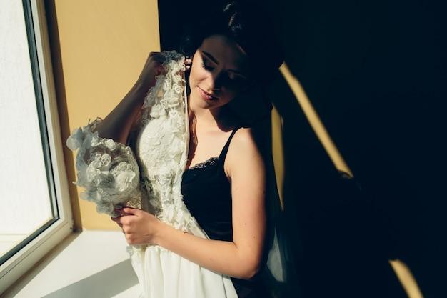 Mariée assise sur un rebord de fenêtre et tient la robe de mariée