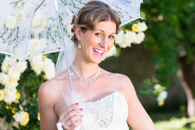 Mariée au mariage avec parasol dans le jardin d'été
