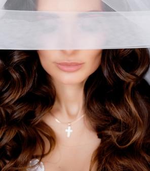 Mariée aux longs cheveux bruns avec des boucles aux yeux fermés couverts de voile