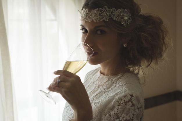 Mariée ayant un verre de champagne à la maison