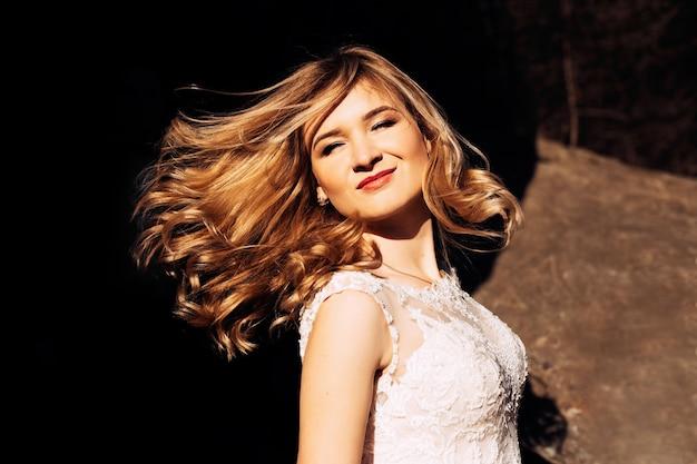 Mariée avec un beau maquillage et une coiffure ondulant ses cheveux au soleil