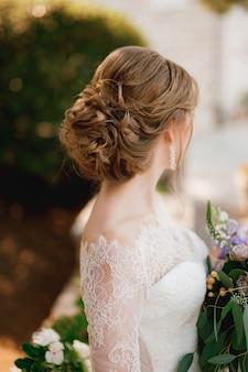 Une mariée avec une belle coiffure dans une robe en dentelle se tient avec un bouquet et regarde sur le côté