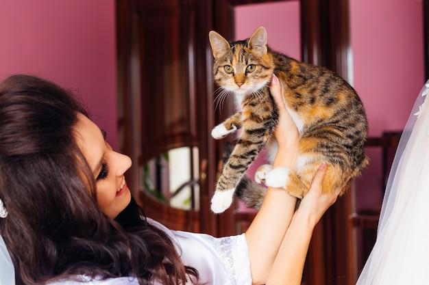 Mariée avec une belle coiffure et maquillage tient un chat dans son bras