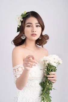 Mariée de belle femme asiatique sur fond gris. portraits en gros plan avec un maquillage professionnel