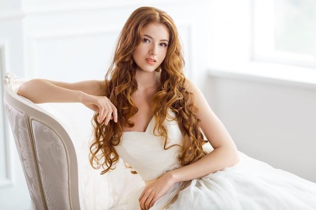Mariée en belle robe assise reposant sur un canapé à l'intérieur