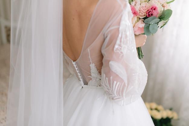La mariée en belle robe est titulaire d'un bouquet de mariée.