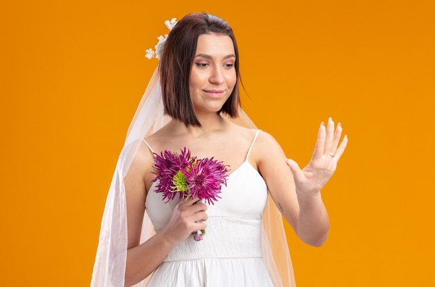 Mariée en belle robe de mariée avec bouquet de fleurs en regardant sa bague à son doigt debout sur un mur orange