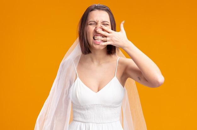 Mariée en belle robe de mariée heureuse et excitée montrant la paume avec un anneau sur son doigt mordant le doigt