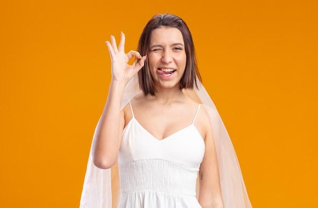 Mariée en belle robe de mariée heureuse et joyeuse qui sort la langue montrant un signe ok debout sur un mur orange