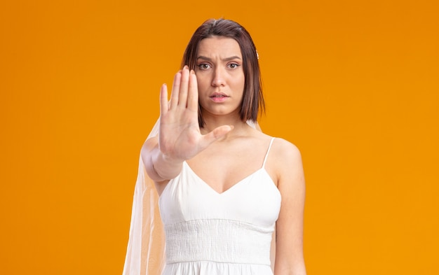 Mariée en belle robe de mariée avec un visage sérieux faisant un geste d'arrêt avec une main ouverte debout sur un mur orange