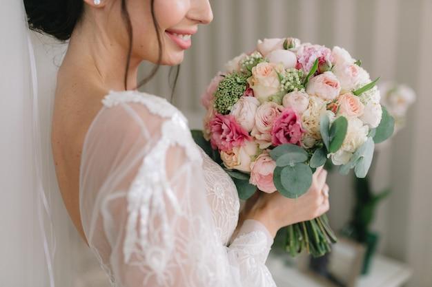La mariée en belle robe sourit et tient un bouquet de mariée.