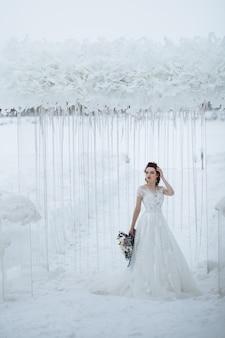 Mariée avec belle sur le tournage d'hiver de mariage sur le fond du paysage d'hiver de mariage
