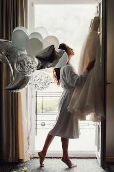 Mariée en blanc en regardant sa robe