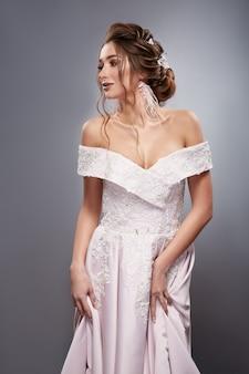 Mariée blanche caucasienne en robe de mariée blanche isolée sur fond gris