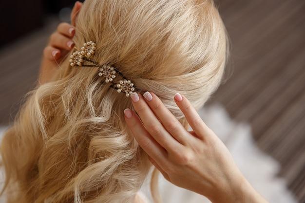 Mariée blonde ajuste sa coiffure au jour du mariage