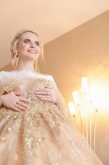 Mariée blonde souriante dans une robe beige chic dans une chambre d'hôtel
