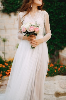 Une mariée avec un bouquet dans ses mains se tient au mur d'une maison avec une liane verte et orange