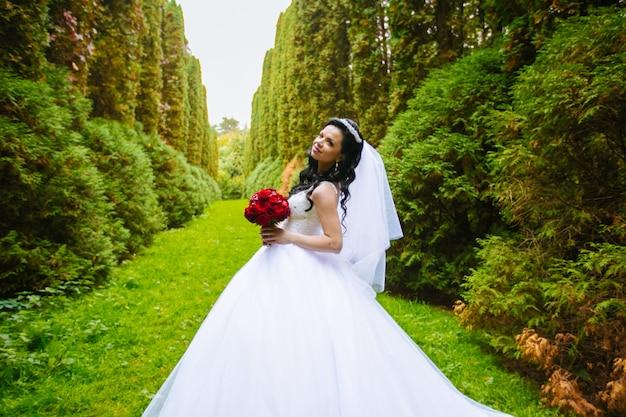 Mariée avec un bouquet debout au soleil dans le parc