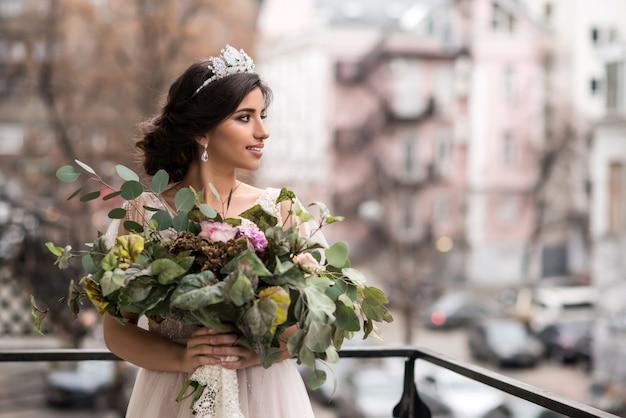 Mariée avec un bouquet de fleurs sur le balcon parmi les rues de la grande ville